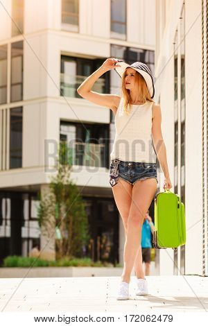 Travel adventure teenage journey concept. Walking woman wearing denim shorts white top and sun hat suitcase holding suitcase on wheels
