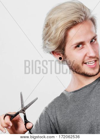 Coiffure hairstyle and haircut. Young cool guy holding special shears tool for work of hairdresser.