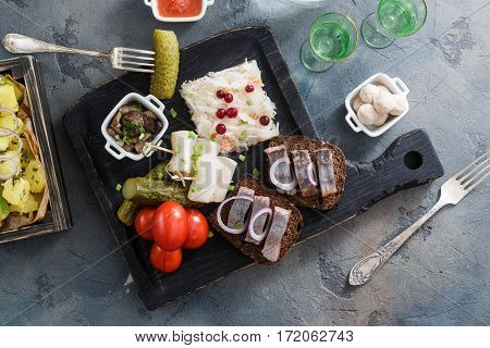 Appetizer food, herring and rye bread on wooden board with vodka and pickles.