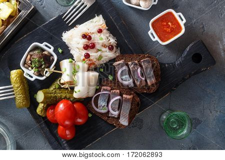 Traditional snacks salted herring, cod caviar, with vegetables, onion, lard, bread, potato and two shots of vodka
