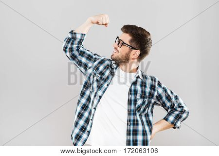 Man in checked T-shirt and eyeglasses with hand up. Showing strength. Looking aside, clenched fist, smiling. Indoors, studio, waist up, profile