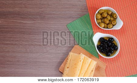 Black and green olives in oil and slices of cheese on a wooden background. View from above. Free space for text