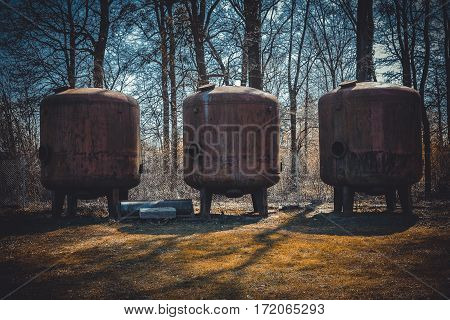 Three Old Rusty Metal Container In A Secluded Forest