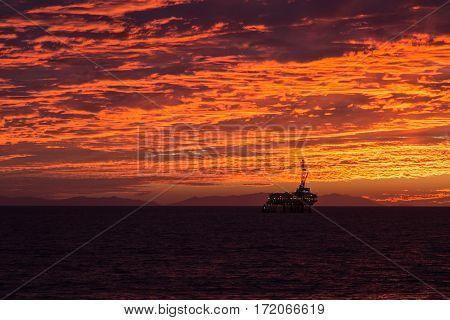 Offshore oil rig silhouetted by an orange cloud filled sky