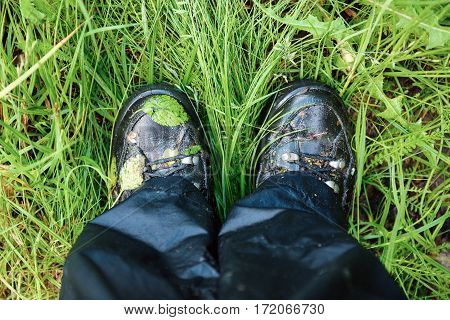 Close up of dirty and wet trekking boots on the green grass with leaves. Travel adventure and sport concept of lifestyle