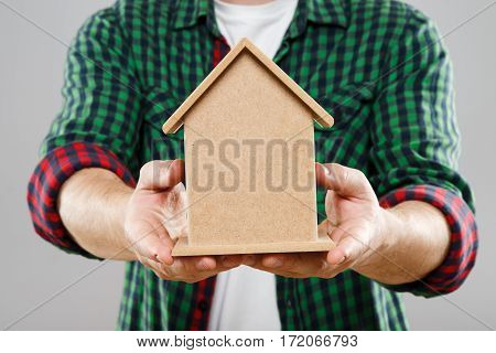 Man in green checked T-shirt holding little wooden house, mini model of house. Close up, without head. Indoors, studio
