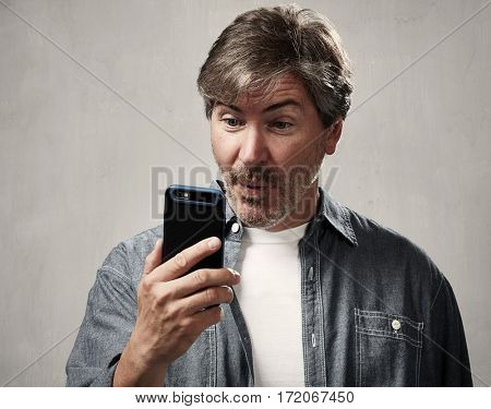 Smiling young man with smartphone over gray background
