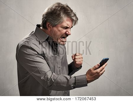 Angry Man reading message on mobile phone