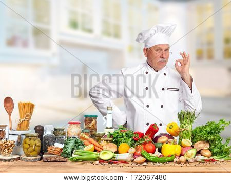 Chef man in kitchen over food vegetables background.
