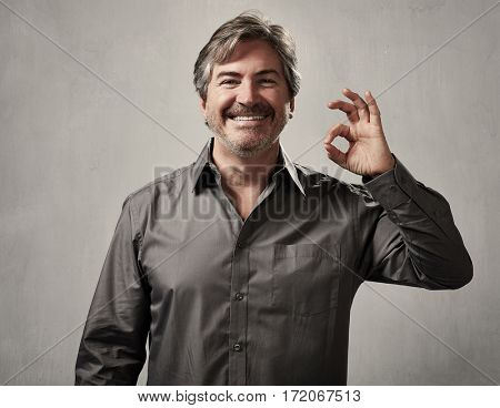 Happy excited lucky man over gray wall background