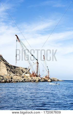 An ocean front rock quarry being mined using cranes and derricks during a colorful, bright day