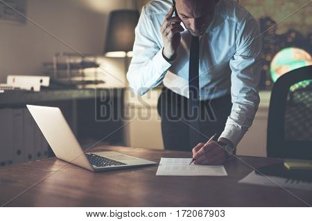 Serious Businessman Signing Document