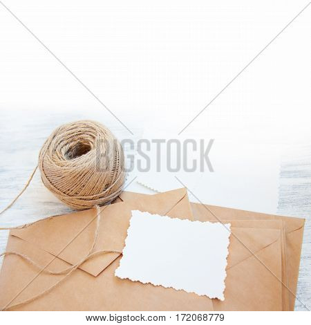 Vintage stillife with brown rough paper envelopes, skein of cord and blank white empty card