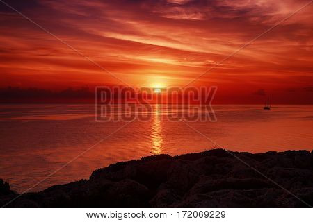 Beautiful colorful sunrise at the sea with dramatic clouds and sun shining