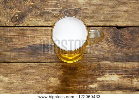 ight beer mug with foam on the wooden surface.view from above