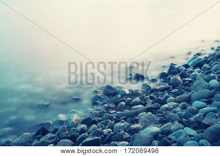 Dreamy natural background with sea shore, rocks and waves. Long exposure