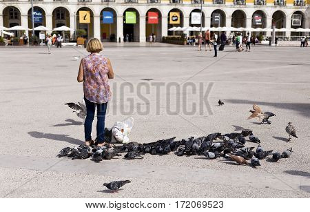 LISBON, PORTUGAL - September 27, 2016: Woman feeding the birds pigeons and seagulls in Commerce Square the main public square in downtown Lisbon Portugal