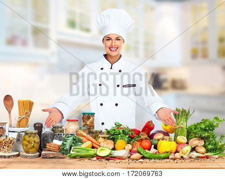 Beautiful Chef woman on food vegetables background.