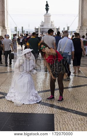 LISBON, PORTUGAL - September 26, 2016: Tourist taking a selfie with a busker living statue in downtown Lisbon Portugal