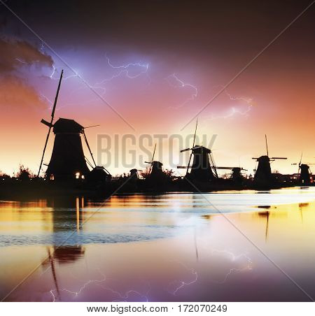 Lightning in cloudy dark sky. Traditional Dutch windmills canal in Rotterdam. Wooden pier near the shore of the lake. Holland. Netherlands.