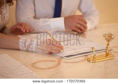 Bride and groom at the registration desk sign documents