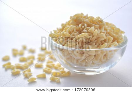 Alphabet pasta for children's meals. ABC pasta. Dry pasta in a glass bowl isolated on white