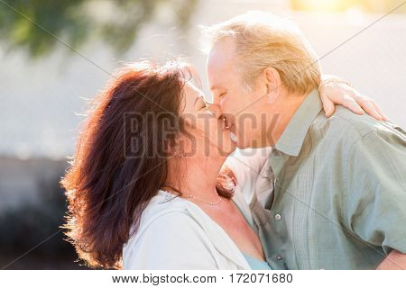 Happy Middle Aged Couple Enjoy A Romantic Slow Dance And Kiss Outside.