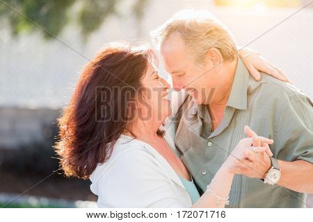 Happy Middle Aged Couple Enjoy A Romantic Slow Dance Outside.