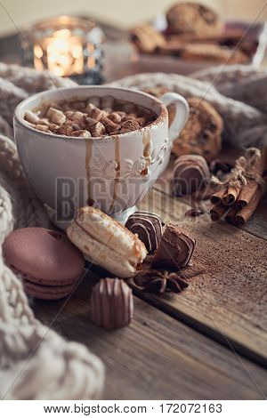 Christmas or New Year composition with hot chocolate or cocoa and marshmallows decorated with sweets spices and knitted scarf. Winter holidays background.