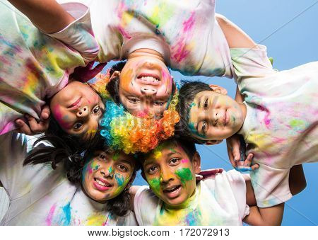 five Indian kids making circle on holi, Asian small kids or siblings or friends with heads together in round, with faces coloured with gulal