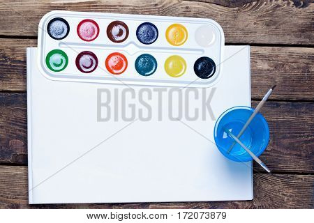 palette of watercolor paints, brushes and cup sheet of blank paper on a wooden surface.top view