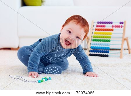 delighted happy infant baby playing on carpet at home