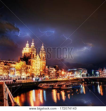 Amsterdam canal. Lightning strike on the cloudy dark sky. Fantastic summer night scene.