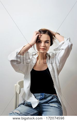attractive sexy fashion model with is posing on chair and hold hands hair in jeans and shirt in studio for glamour vogue test photo shoot