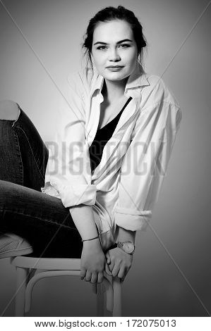 attractive sexy fashion model is posing on chair in jeans and shirt in studio for glamour vogue test photo shoot