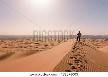 A man, standing on one of the highest dunes in the Sahara desert near Merzouga, overlooks the dunes of the Erg Chebbi at sunrise.