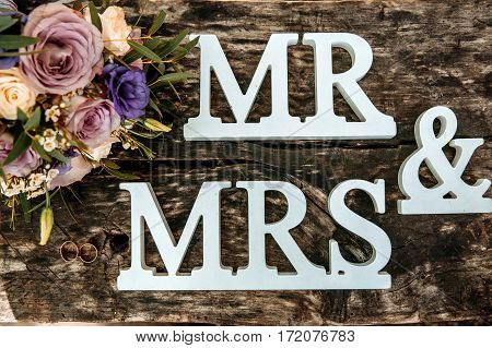 Wedding bouquet and rings on wooden surface. Wedding rings. Wedding simbols. Wedding bouquet background.