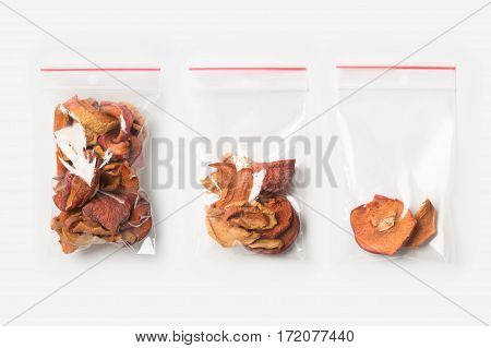 Set of three EMPTY, HALF AND FULL Plastic transparent zipper bag with home dried apples isolated on white. Vacuum package mockup with red clip. Concept
