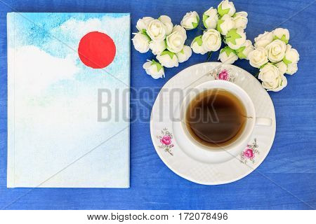 Book on the blue table with herbal tea and flowers