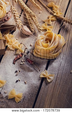 Raw homemade pasta with flour and spices on the rustic background. Uncooked noodles.