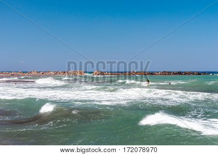 Stormy coastline of Santorini island with surfer on waves