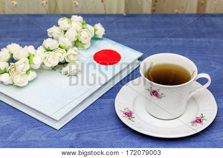 Herbal tea with book on blue table