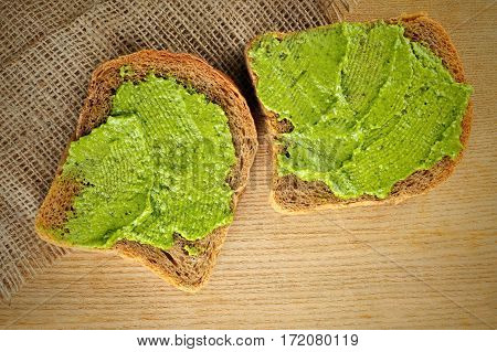 whole grain bread with fresh basil pesto on wooden board