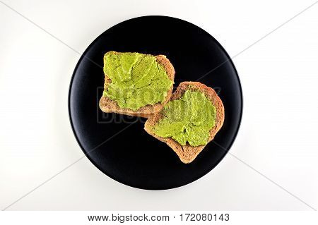bread with fresh basil pesto on wooden board on black plate