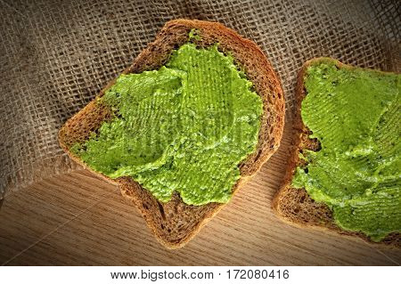whole grain bread with fresh basil pesto on wooden board, top view