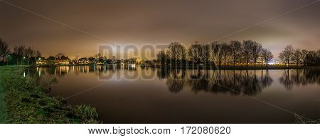 Peaceful panoramic view of the Amstel river and trees while city lights from Amsterdam illuminate the night sky in the background