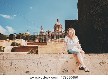 Plus size girl smiling and looking into camera while while sitting on stairs in sunny day blonde girl in white t-shirt and grey skirt is enjoying bright morning with copy space area for your message