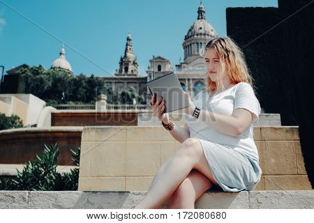 Plus size model girl making online shopping via her digital tablet while sitting on stairs in sunny day blonde girl in white t-shirt and grey skirt is chatting online with her family using touch pad