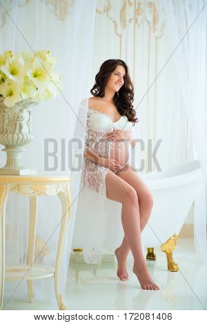 Gentle pregnancy. Beautiful pregnant in light white lace negligee in the bathroom.
