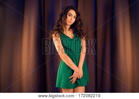 Fashion studio shot of beautiful brunette woman with makeup and curly hairstyle wearing evening green dress on brown silk background.